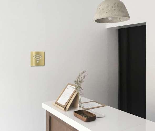 Messing Hinweisschild WLAN WIFI Schild Gold auf weißer Wand